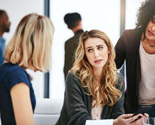 Three women in an office discuss a serious matter